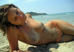 Cute young girlfriend posing topless on beach